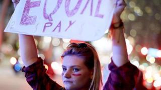 Mulher segura cartaz exigindo salários iguais