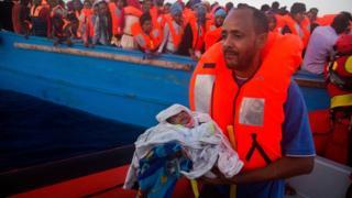 Un homme porte son fils âgé de cinq jours sur l'une des embarcations de sauvetage.