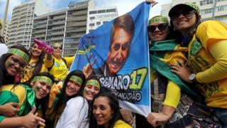Mulheres com camisas verde amarelo seguram bandeira com rosto de Bolsonaro