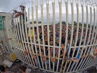 Honduran migrants wait behind a gate after crossing the fence on the border with Guatemala to enter Mexico