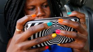 Ugandan woman with painted nails using a cell phone.