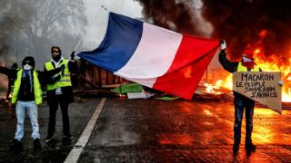 Protesters hold a French flag near a burning barricade during a protest of Yellow vests