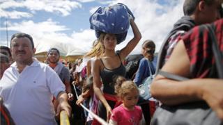 Граница Венесуэлы и Колумбии, женщина стоит в очереди купить продукты