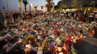 This file photo taken on July 18, 2016 shows People standing in front of flowers, candles and messages laid at a makeshift memorial in Nice in tribute to the victims of the deadly attack on the Promenade des Anglais seafront which killed 86 people.