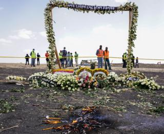 Candles burn before a flower adorned memorial arch erected at the site of the Ethiopian Airlines Flight ET302 crash on March 14, 2019 in Ejere, Ethiopia.