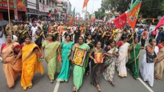 Women with flags walking on a street protesting