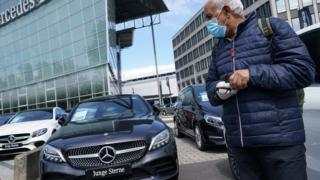 A man wearing a surgical mask stands at a Mercedes-Benz dealership where he said he is considering buying a car during the coronavirus crisis on May 05, 2020 in Berlin, Germany.