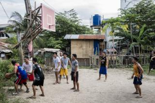 Men shoot hoops in the Visayan Region of the Philippines