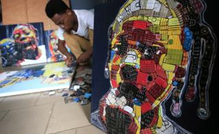 Artist Desire Koffi making works of art from used telephone keyboards at his workshop in Abidjan, Ivory Coast - Thursday 24 January 2019