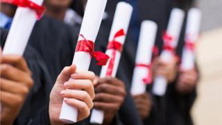 University students holding diploma certificates