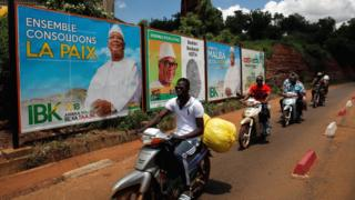 People ride their motorcycle past electoral billboards of Ibrahim Boubacar Keita, the Malian president