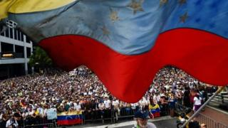 "A Venezuelan national flag flutters during a mass opposition rally against President Nicolas Maduro in which Venezuela""s National Assembly head Juan Guaido (out of frame) declared himself the country""s ""acting president"", on the anniversary of a 1958 uprising that overthrew a military dictatorship"