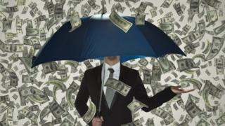 Person stood beneath an umbrella and lots of money