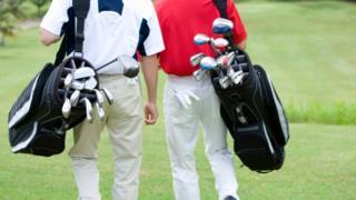 Two golfers walking.