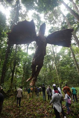 People in a forest walk past a large statue hovering overhead.