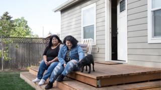 Sherry Mesa (E) e sua sobrinha, Sobeyda (D), sentadas em frente à microcasa em que vivem desde julho no quintal de Martha Chambers, nos EUA. Elas antes eram sem-teto