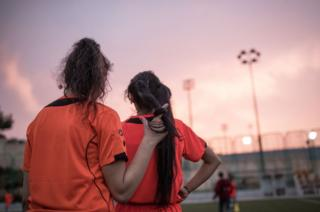 Two girls watch their training session from the sidelines.
