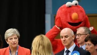 Theresa May participa de divulgação dos resultados da eleição, com homem fantasiado ao fundo