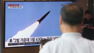 People watch missile launch on television