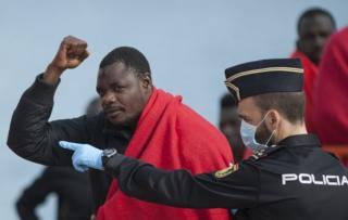 Un inmigrante de raza negra alza el puño mientras es custodiado por un policía español