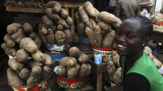 A young woman at a market stall which sells yams