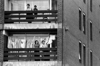 Local residents are pictured watching the gather. Two National Front supporters cheer and clap from the balcony of their tower block flat.