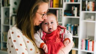 Pia being held by her mother, Ellen De Meyer