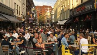 People sit outside restaurants and bars in London's Soho district on Saturday 19 September 2020