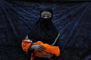 Minara Begum, de 18 años, posa con su bebé enferma de nueve días de nacida. No ha visto a su marido desde hace 15 días, cuando tuvo que escapar de Myanmar porque el ejército quemó su casa.