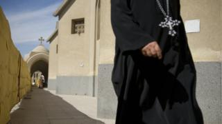 A Coptic Christian priest enters Saint Mark's Cathedral on November 4, 2012 in Cairo,