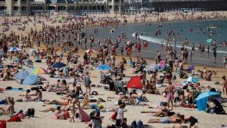 People basking on La Concha beach in San Sebastian, Spain