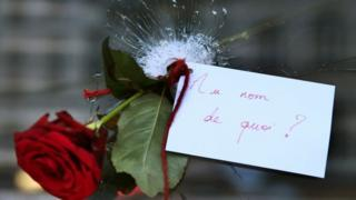 "A rose is placed in a bullet hole in a restaurant window a day after the 13 November attacks in Paris. The note reads ""In the name of what?"""