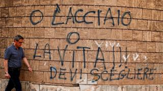 "A man in Taranto, Italy, walks past graffiti reading: ""Steel or life, you have to choose."" It is a reference to the high-polluting Ilva steel plant in Taranto, 27 April 2018"