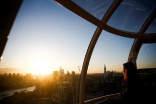 Žena posmatra svitanje sa Londonskog Oka