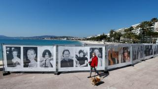 A woman walks past photos of the Cannes Film Festival on the Croisette in Cannes as a lockdown is imposed to slow the rate of the coronavirus in France, March 18, 2020.