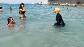 Tesettür mayo (burkini) ile denize giren bir kadın