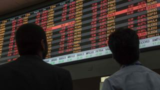 Homens observam painel com dados sobre o mercado de ações