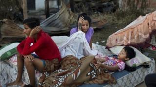 A Ecuadorian family sleeps outside following a powerful earthquake