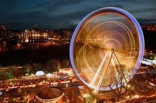Members of the public enjoy a ride on a ferris wheel