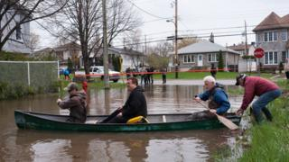 Residents in a canoe paddle on the flooded streets in Pierrefonds on Sunday May 7, 2017.