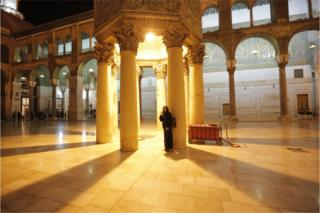A Syrian woman stands in the courtyard of the Umayyad Mosque after the evening prayer in Damascus, Syria, 13 June 2018, as part of preparations for Eid al-Fitr.