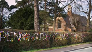 Wool message in hedgerow