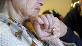 Carer holding woman's hand