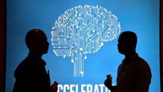 Участники Intel's Artificial Intelligence (AI) Day на фоне постера во время мероприятия в индийском городе Бангалор, 4 апреля 2017 года