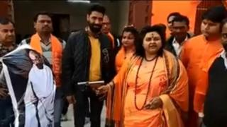 Pooja Pandey, leader of the Hindu Mahasabha, shooting at an effigy of Gandhi with an air pistol