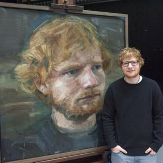 Ed Sheeran stands beside his portrait by Colin Davidson