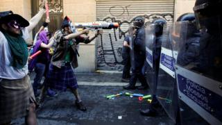 A protester squirts a water gun at Catalan regional police