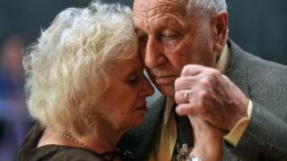 Señores mayores bailando tango.