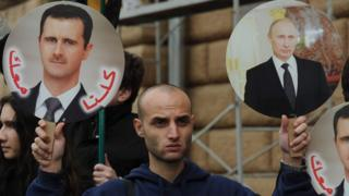 A pro-regime supporter holds photos of President Assad and President Putin