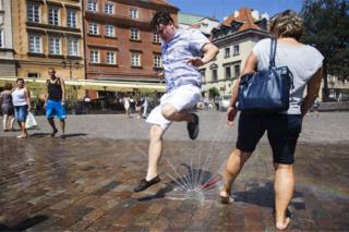 People cool themselves with sprinklers during the heat wave in Warsaw